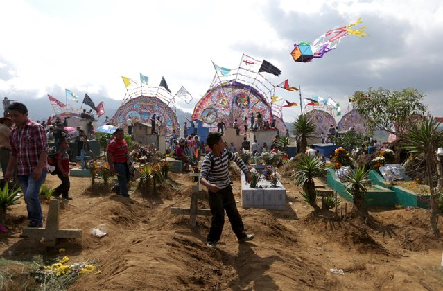 A boy flies a kite over a graves in the cemetery of Santiago Sacatepequez, Guatemala, November 1, 2015. (Photo by Jorge Dan Lopez/Reuters)