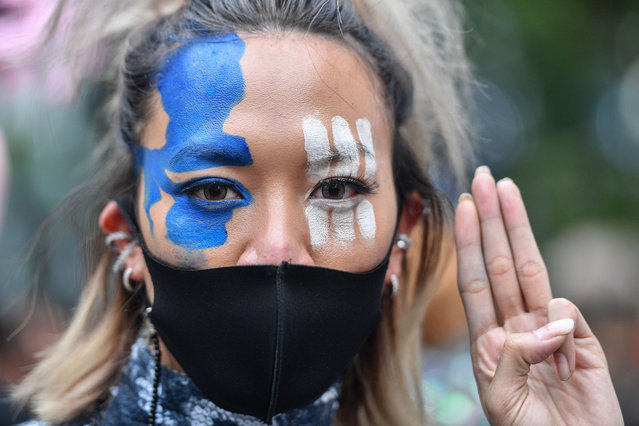 A pro-democracy protester wearing face paint and a mask holds up the three-finger salute during an anti-government rally in Bangkok on October 25, 2020. (Photo by Mladen Antonov/AFP Photo)