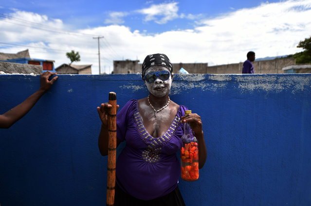 A voodoo devotee in the role of a spirit known as a Gede is seen during ceremonies honoring the Haitian voodoo spirits of Baron Samdi and Gede on the Day of the Dead in the Cemetery of Cite Soleil, in Port-au-Prince, Haiti on November 2, 2015. Revelers streamed into cemeteries across Haiti bearing beeswax candles, food offerings and bottles of rum infused with hot peppers to mark the country's annual Voodoo festival of the dead. (Photo by Hector Retamal/AFP Photo)
