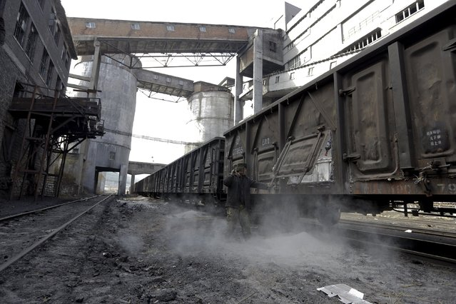A worker opens a door of carriage as it is cleaned to load coal outside a coal mine of the state-owned Longmay Group on the outskirts of Jixi, in Heilongjiang province, China, October 22, 2015. (Photo by Jason Lee/Reuters)