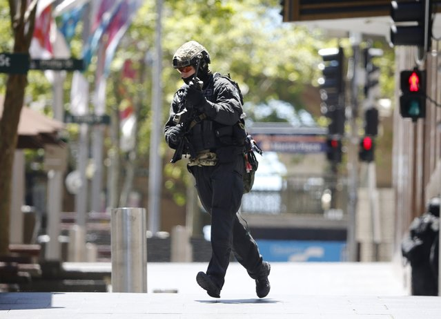 A police officer runs across Martin Place near Lindt Cafe where hostages are being held, in central Sydney December 15, 2014. (Photo by Jason Reed/Reuters)