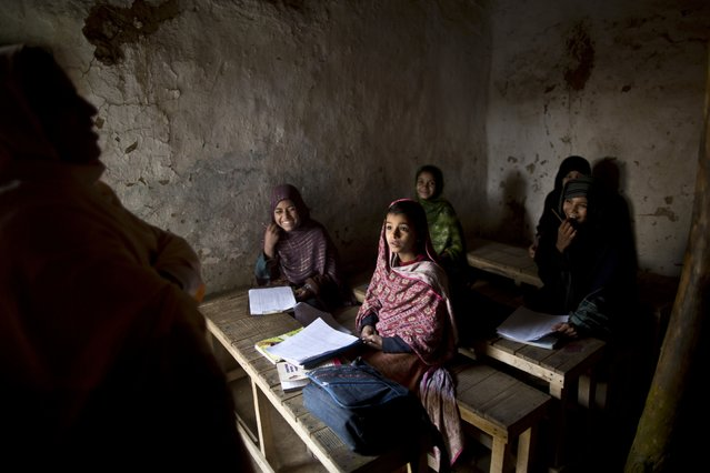 Afghan refugees and internally displaced Pakistani school girls laugh with their teacher during an exam at a makeshift school on the outskirts of Islamabad, Pakistan, Friday, December 19, 2014, days after Taliban fighters killed 148 people – most of them children – in a school massacre. (Photo by Muhammed Muheisen/AP Photo)