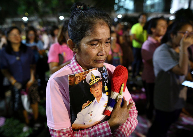 A woman holds a picture of Thailand's King Bhumibol Adulyadej after an announcement that he has died, at the Siriraj hospital in Bangkok, Thailand, October 13, 2016. (Photo by Athit Perawongmetha/Reuters)