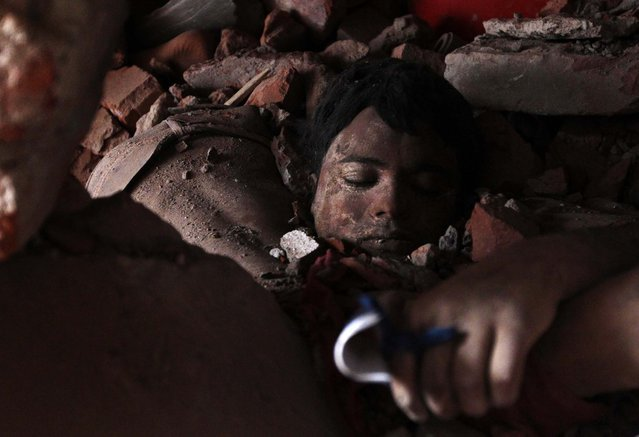 A victim's body lies amidthe remains of the building on Thursday. (Photo by A. M. Ahad/Associated Press)