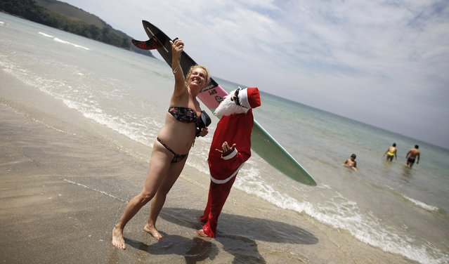 "Carlos Bahia, dressed as Santa Claus, poses for a ""selfie"" with a woman at the Maresias beach, in the state of Sao Paulo December 9, 2014. (Photo by Nacho Doce/Reuters)"