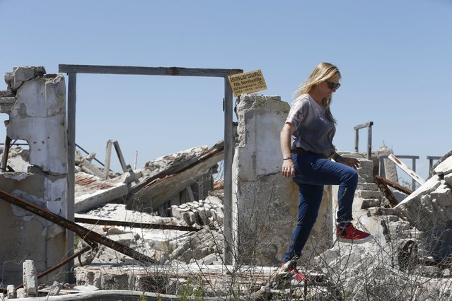 Viviana Castro, a former resident walks by ruined houses in the onetime spa and resort town Epecuen, November 6, 2015. (Photo by Enrique Marcarian/Reuters)