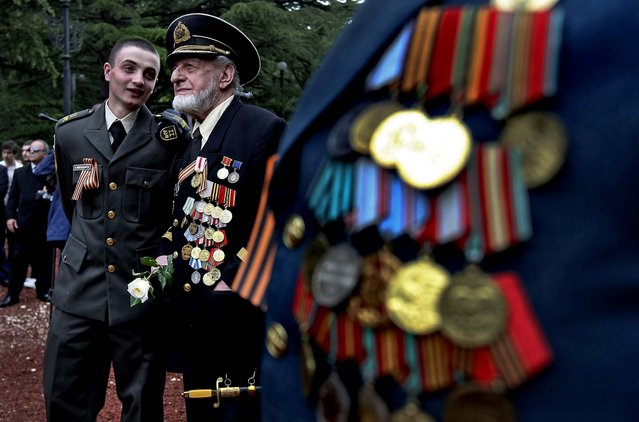 A Georgian military cadet speaks with a WW II veteran at a WW II memorial during Victory Day celebration in Tbilisi, as Georgia celebrates the 68th anniversary of the Soviet Union's victory over Nazi Germany. (Photo by Shakh  Aivazov/Associated Press)