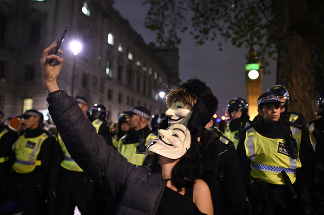 Masked protesters take a selfie in front of the Houses of Parliament during the Million Mask March on November 5, 2015 in London, England. The annual anti-establishment protest is organised by activist group Anonymous and is one of hundreds expected to take place in cities across the globe this evening. (Photo by Ben Pruchnie/Getty Images)