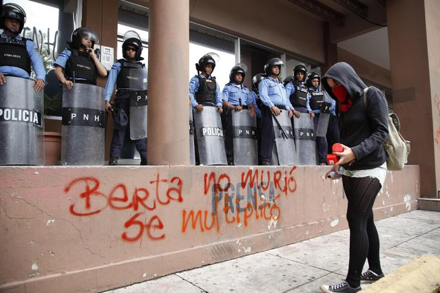 """A protester writes with spray paint """"Berta did not die, she multiplied"""" in front of riot police guarding the attorney general's office in Tegucigalpa, Honduras, Thursday, October 20, 2016. Members of the Civic Council of Popular and Indigenous Organizations of Honduras (COPINH) and people belonging to the Garifuna people protested to demand justice over the March 2016 murder of Honduran indigenous leader and environmentalist Berta Caceres and to halt construction of the Agua Zarca dam, which would displace many of the indigenous Lenca people. (Photo by Fernando Antonio/AP Photo)"""
