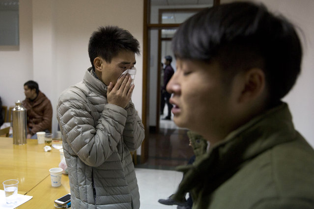 A man who only gave his surname Zhao cries after seeing a photo of his girlfriend Pan Haiqin who was killed in the deadly stampede in Shanghai, China, Friday, January 1, 2015. (Photo by Ng Han Guan/AP Photo)