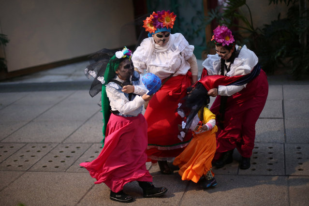"People with their faces painted to look like the popular Mexican figure called ""Catrina"" protect themselves from the wind in a procession to celebrate the upcoming annual Day of the Dead on November 1 and 2, at Reforma avenue, in Mexico City, Mexico, October 23, 2016. (Photo by Edgard Garrido/Reuters)"