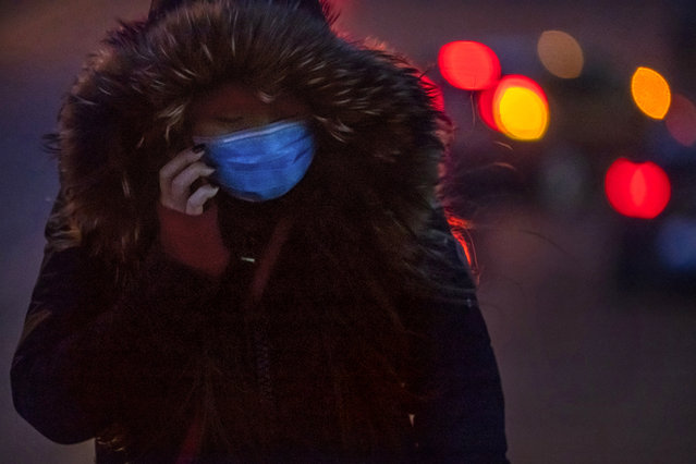 A commuter wearing a face mask to protect against the spread of the coronavirus walks along a street on an unseasonably cold day in Beijing, Tuesday, December 30, 2020. Beijing has urged residents not to leave the city during the Lunar New Year holiday in February, implementing new restrictions and mass testings after several coronavirus infections last week. (Photo by Mark Schiefelbein/AP Photo)