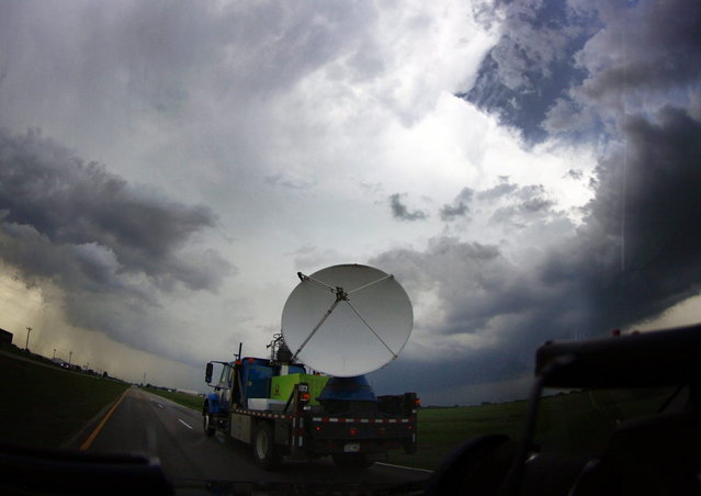 A National Oceanic and Atmospheric Administration (NOAA)'s mobile doppler radar mounted on the back of a truck tracks a tornadic thunderstorm passing over Clearwater, in Kansas May 19, 2013. A massive storm front swept north through the central United States on Sunday, hammering the region with fist-sized hail, blinding rain and tornadoes, including a half-mile wide twister that struck near Oklahoma City. News reports said at least one person had died. The picture was taken through a car window. (Photo by Gene Blevins/Reuters)