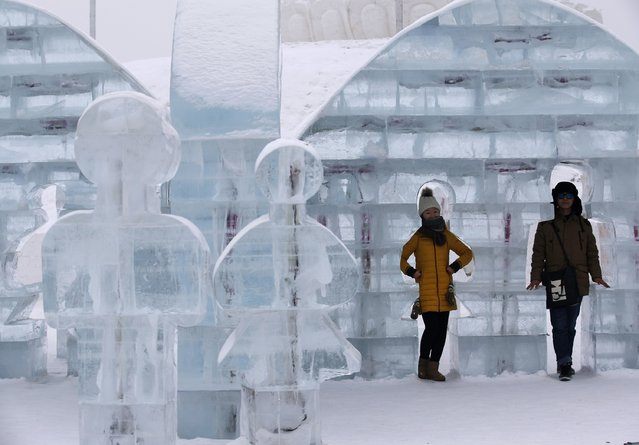 A couple takes a picture with an ice sculpture ahead of the 31st Harbin International Ice and Snow Festival in the northern city of Harbin, Heilongjiang province, January 4, 2015. (Photo by Kim Kyung-Hoon/Reuters)