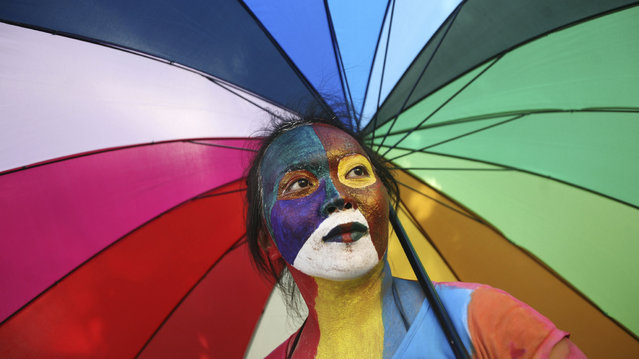 An Indonesian activist with painted face holds an parasol during a protest demanding equality for LGBTIQ (Lesbian, gay, bisexual, transgender and questioning) people in Medan, North Sumatra, Indonesia, Friday, May 31, 2012. Homosexuals and transgenders in the world's most populous Muslim country are often faced with discriminations and abuses. (Photo by Binsar Bakkara/AP Photo)
