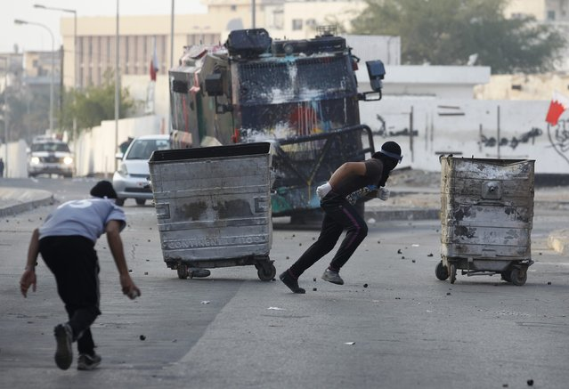 Protesters run for cover as a riot police armoured personnel carrier charges at them during clashes in the village of Bilad Al Qadeem, south of Manama, January 5, 2015. Bahraini police fired rubber bullets and tear gas to scatter protesters who gathered outside the home of Sheikh Ali Salman, a Shi'ite Muslim opposition leader on Monday, witnesses said, after he was remanded in custody for a further 15 days. (Photo by Hamad I. Mohammed/Reuters)
