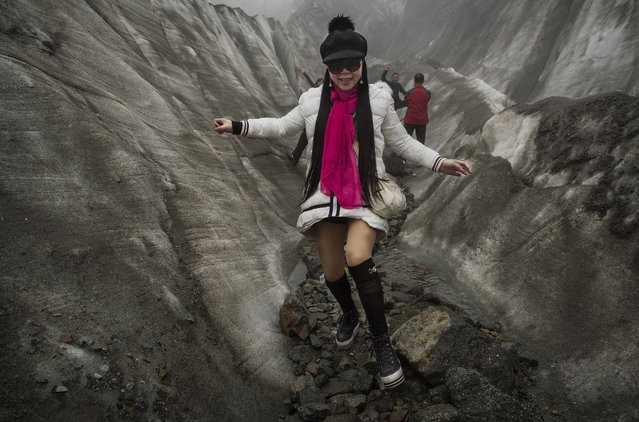 A Chinese tourist walks in the tongue of Glacier 1 at the base of the 7,556 m (24,790 ft) Mount Gongga, known in Tibetan as Minya Konka on November 10, 2015 in Hailuogou, Garze Tibetan Autonomous Prefecture, Sichuan province, China. Hailuogou is one of China's 8,500 monsoonal glaciers and the longest of 71 glaciers on the eastern slope of Mt. Gongga. Monsoonal glaciers are found at lower altitudes and are at much higher risk to the effects of rising temperatures and climate change. (Photo by Kevin Frayer/Getty Images)