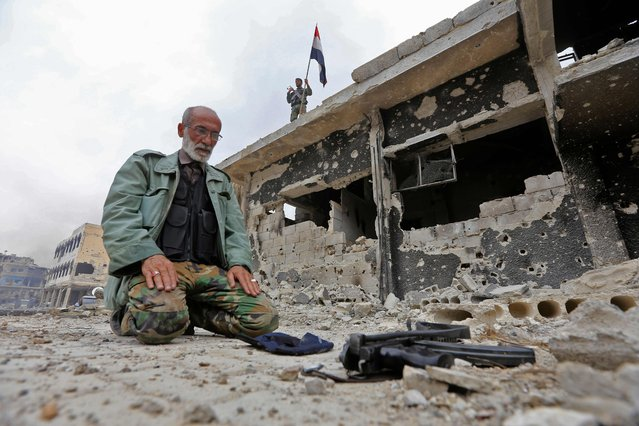A member of the Syrian pro-government forces prays in a destroyed street in the Hajar al-Aswad neighbourhood on the southern outskirts of the capital Damascus on May 22, 2018. The government seized earlier in the week the Yarmuk Palestinian camp and adjacent neighbourhoods of Tadamun and Hajar al-Aswad from the Islamic State (IS) group , putting Damascus fully under its control for the first time since 2012. (Photo by Louai Beshara/AFP Photo)