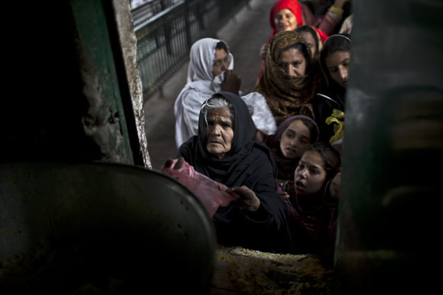 An elderly Pakistani woman asks for rice during a donated food distribution on the occasion of Prophet Muhammad's birthday at a shrine in Islamabad, Pakistan, Sunday, January 4, 2015. (Photo by Muhammed Muheisen/AP Photo)