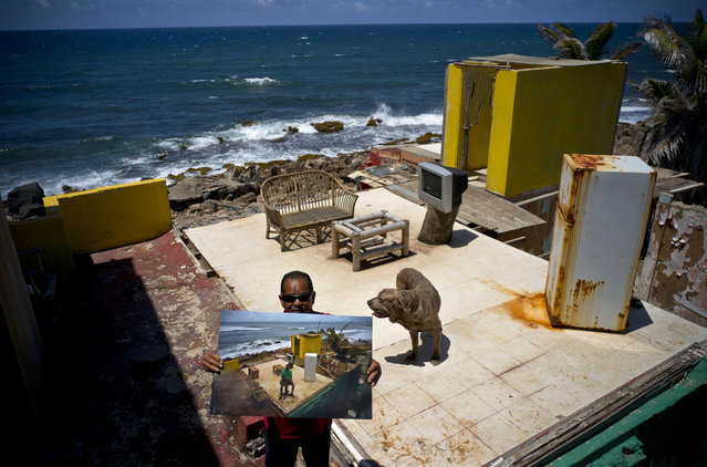 Roberto Figueroa Caballero holds a printed photo taken on October 5, 2017 of him amid his seaside home that was destroyed by Hurricane Maria, as he stands on the same property with his pet dog in the La Perla neighborhood of San Juan, Puerto Rico, May 29, 2018. Figueroa, who found a job at a pizzeria, aims to rebuild his home and is appealing FEMA's second rejection of his application. Figueroa's dog was not allowed to go with him to a donated apartment where he lives now, so he visits his property daily to feed and care for him. (Photo by Ramon Espinosa/AP Photo)