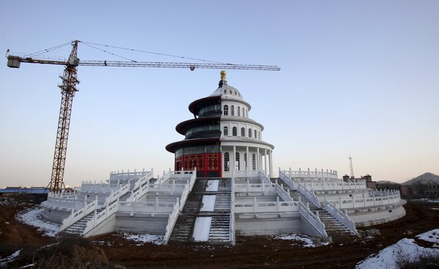A building, which is made by half of a replica of the Qinian Hall of the Temple of the Heaven (L) and half of a western building, is seen under construction at a studio for productions of films and television shows on the outskirts of Shijiazhuang, Hebei province, China, December 3, 2015. (Photo by Reuters/Stringer)