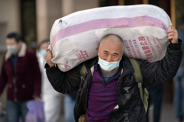A traveler wearing a face mask to protect against the spread of the coronavirus carries his luggage as he walks out of an exit at the Beijing Railway Station in Beijing, Thursday, January 28, 2021. (Photo by Mark Schiefelbein/AP Photo)
