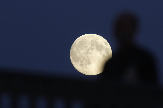 """The moon rises over the Ioannovsky Bridge as a pedestrian walks across in St. Petersburg June 22, 2013. The largest full moon of the year, called the """"supermoon"""", will light up the night sky this weekend. (Photo by Alexander Demianchuk/Reuters)"""