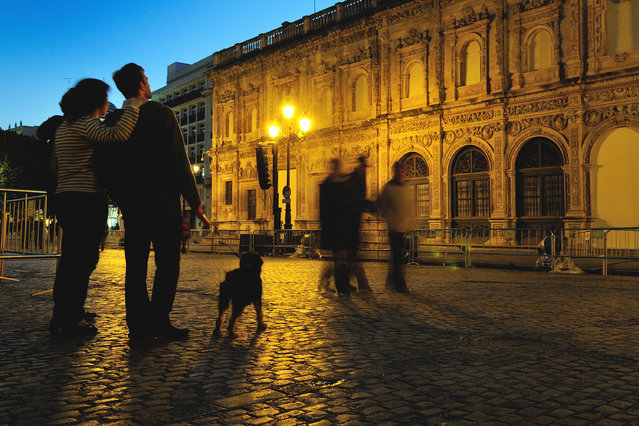 """Enjoing Seville"". A couple with their pet watching the baroque style facade of the City Town Hall in Plaza San Francisco at Seville, Spain. It was twilight of a January day yet the fantastic climate of Andalucia welcomed people to take a walk just wearing a sweater. (Photo and caption by Stefano Spezi/National Geographic Traveler Photo Contest)"
