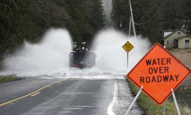 A truck drives through flood waters of the Snoqualmie River covering Ames Lake Carnation Road NE during a storm in Carnation, Washington December 9, 2015. (Photo by Jason Redmond/Reuters)