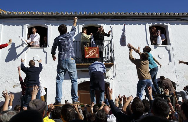 People try to catch ham legs thrown from a house during the annual San Antonio Abad (Saint Anton Abbott) festival in Trigueros, southwest Spain January 25, 2015. (Photo by Marcelo del Pozo/Reuters)