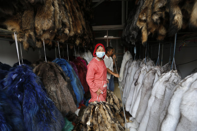 A worker hangs bundles of mink fur inside a store at a fur market in Chongfu township, Zhejiang province September 13, 2013. (Photo by Reuters/Stringer)