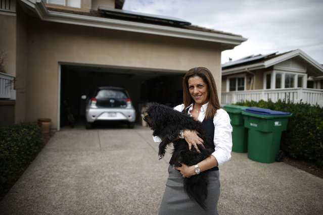 Computer science professor Christa Lopes stands next to her home and her Scion IQ electric car in Irvine, California January 26, 2015. (Photo by Lucy Nicholson/Reuters)