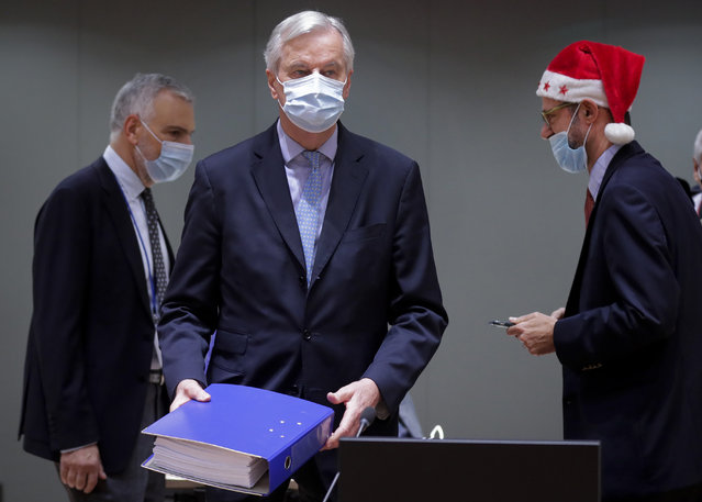 A colleague wears a Christmas hat as European Union chief negotiator Michel Barnier, center, carries a binder of the Brexit trade deal during a special meeting of Coreper, at the European Council building in Brussels, Friday, December 25, 2020. European Union ambassadors convened on Christmas Day to start an assessment of the massive free-trade deal the EU struck with Britain. After the deal was announced on Thursday, EU nations already showed support for the outcome and it was expected that they would unanimously back the agreement, a prerequisite for its legal approval. (Photo by Olivier Hoslet, Pool via AP Photo)