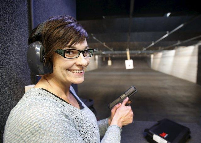 First time gun owner, Jessie Palmieri holds her new H&K VP9 9mm gun at the Ringmasters of Utah gun range, in Springville, Utah on December 18, 2015. (Photo by George Frey/Reuters)