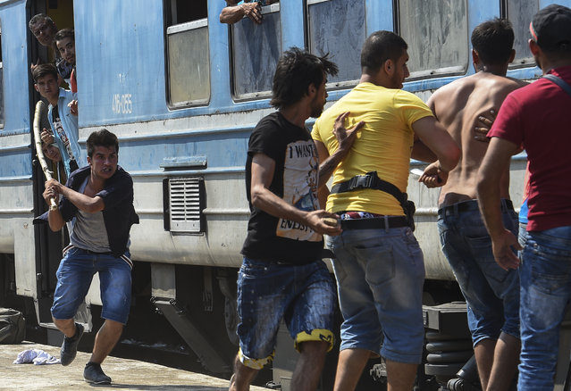Migrants with a stick, stones and knife fight with each other after a brawl erupted over a place in an overcrowded train heading to the Serbian border at the train station in Gevgelija, The Former Yugoslav Republic of Macedonia, 14 August 2015. The number of migrants passing through Macedonia increases day by day, local sources said. From the beginning of the year to mid-June 2015, nearly 160,000 migrants landed in the southern European countries, mainly Greece and Italy, on their way to wealthier countries in Western and Northern Europe, according to estimates by the International Organization for Migration (IOM). (Photo by Georgi Licovski/EPA/EFE)