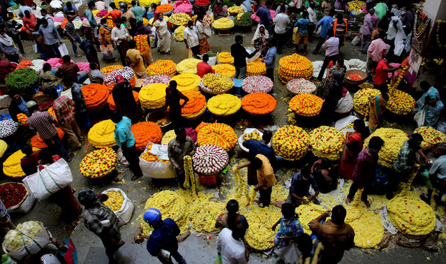 People buy colorful flowers ahead of the Navaratri festival in Bangalore, India, 23 October 2020. Hindus over the world will celebrate the annual Hindu Navratri or Durga Puja festival that represents female power and the victory of good over evil. (Photo by Jagadeesh N.V./EPA/EFE)