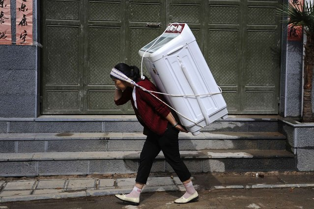 Home delivery: A woman carries a washing machine on her back in Dali, Yunnan province, China, on August 1, 2013. (Photo by Reuters)