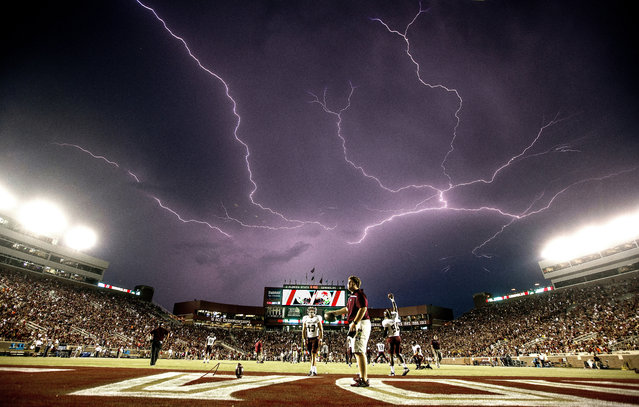 In this September 5, 2015 file photo, a lightning strike occurs as Texas State warms up in Doak Campbell Stadium prior to an NCAA college football game against Florida State in Tallahassee, Fla. Lightning used to kill about 300 Americans a year, but lightning deaths are on pace to hit a record low this year. Scientists say less time spent outside and improved medical treatment have contributed to fewer deaths. (Photo by Mark Wallheiser/AP Photo)