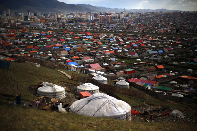 Gers, traditional Mongolian tents, are seen on a hill in an area known as a ger district in Ulan Bator June 28, 2013. Approximately 60 percent of the population of Ulan Bator live in settlements known as ger districts and in many cases residents have limited access to basic services such as water and sanitation. According to a 2010 National Population Center census, every year between thirty and forty thousand people migrate from the countryside to the capital Ulan Bator. Ger districts in the city have been expanding rapidly in recent years. Mongolia is the world's least densely populated country, with 2.8 million people spread across an area around three times the size of France. (Photo by Carlos Barria/Reuters)