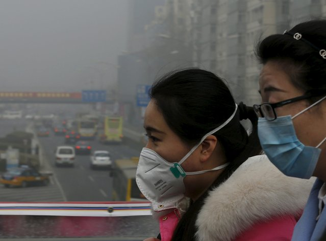 Woman wearing protective masks walk on a heavily polluted day in Beijing, December 25, 2015. (Photo by Kim Kyung-Hoon/Reuters)