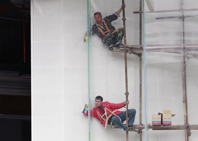 Workers install the glass wall of a building under construction in Guangzhou, Guangdong province, February 5, 2015. (Photo by Alex Lee/Reuters)
