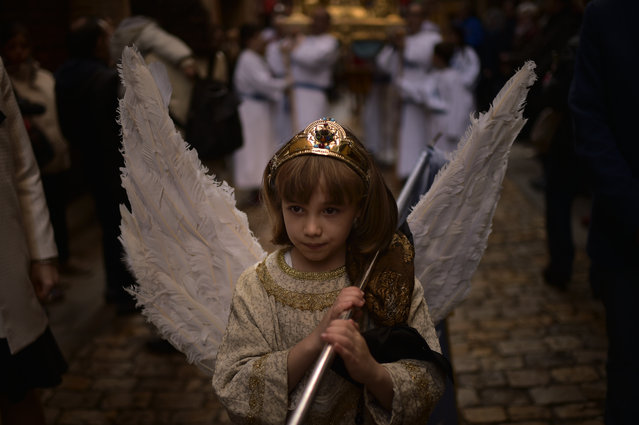 """8 years old Ariadna Vallejo, center, takes part in the Easter Sunday ceremony """"Descent of the Angel"""", during Holy Week in the small town of Tudela, northern Spain, Sunday, April 1, 2018. (Photo by Alvaro Barrientos/AP Photo)"""