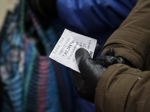 A refugee from eastern Ukraine holds a meal coupon as she stands in a queue to receive food donated to a volunteer centre in Slaviansk February 7, 2015. (Photo by Gleb Garanich/Reuters)