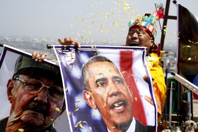 Peruvian shamans holding a poster of Cuba's President Raul Castro and U.S. President Barack Obama perform a ritual of predictions for the new year at Morro Solar hill in Chorrillos, Lima, Peru, December 29, 2015. (Photo by Mariana Bazo/Reuters)
