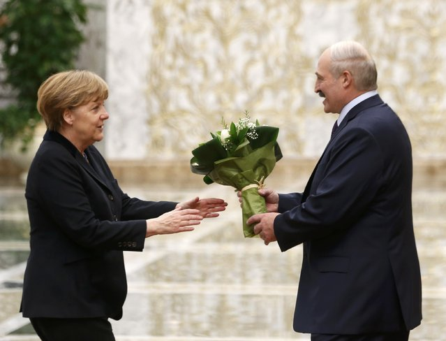 Belarus' President Alexander Lukashenko (R) welcomes Germany's Chancellor Angela Merkel during a meeting in Minsk, February 11, 2015. (Photo by Vasily Fedosenko/Reuters)
