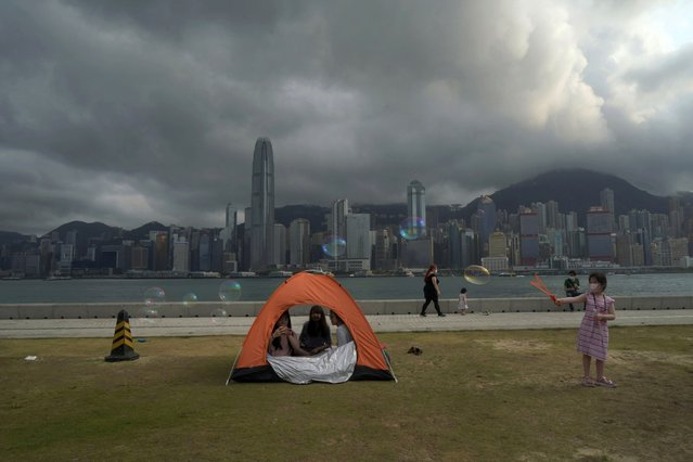 People wearing face masks to help protect against the spread of the coronavirus play at a park in the West Kowloon Cultural District of Hong Kong, Monday, March 29, 2021. The decision not to show a politically sensitive piece of art at an upcoming museum in Hong Kong as well as the Academy Awards this year not airing in the city for the first time in decades has prompted fears that Beijing's crackdown on dissent in Hong Kong has extended into the city's art and entertainment industry. (Photo by Kin Cheung/AP Photo)