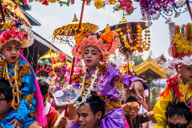 A young boy shows off his dance moves as the group parades through the town in Mae Hong Son, Thailand, April 2016. Monk initiates ditch normal clothes for princely tunics, full make up and heaps of golden jewels for their ordination into Buddhist monkhood. Amongst the Shan people, who live across southeast Asia in northern Thailand and Myanmar, boys between 7 and 14 are annually initiated into their local temples during an elaborate three day ceremony. The young boys don vibrant costumes symbolising Gautama Buddha's days as a prince, before he gave up worldly pleasures, and ride on the shoulders of their male relatives for the three day ceremony. (Photo by Claudio Sieber/Barcroft Images)