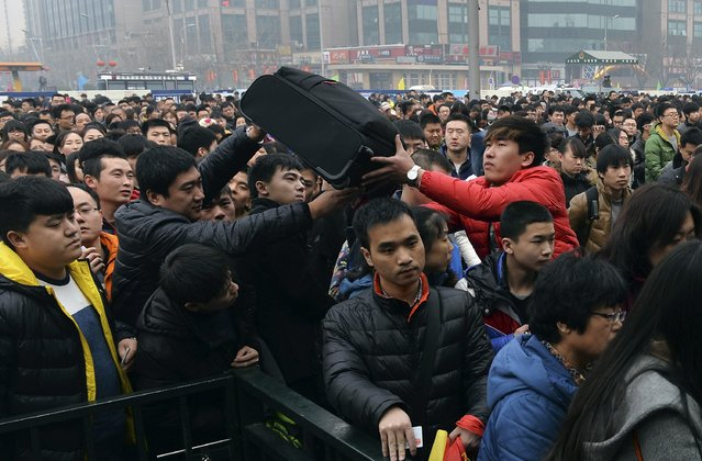 People pass a suitcase as they line up to enter a railway station in Beijing, February 15, 2015. Chinese Ministry of Transport said a total of 2.807 billion trips are expected to be made during the 40-day Spring Festival travel rush, which started on February 4 and will last until March 16, Xinhua News Agency reported. (Photo by Reuters/Stringer)