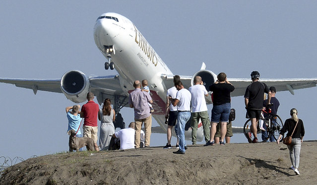 People gather on a hill near the Chopin Airport to watch aeroplanes taking off, in Warsaw, Poland, Sunday, September 9, 2018. (Photo by Alik Keplicz/AP Photo)