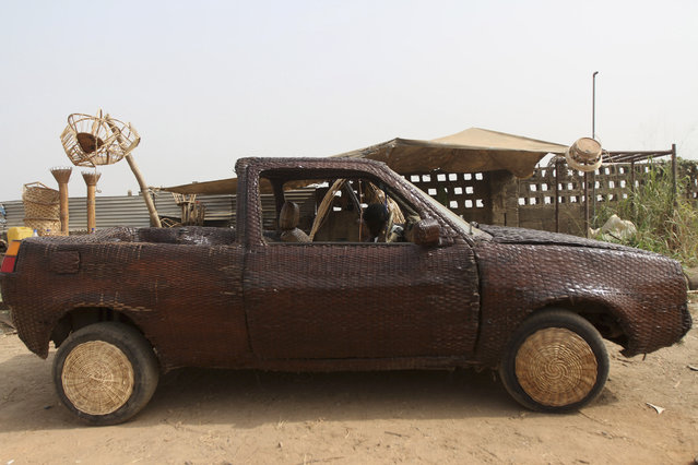 A converted car, which is covered with woven raffia palm cane, is parked in front of an artisan workshop in Ibadan, southwest Nigeria January 10, 2013. (Photo by Akintunde Akinleye/Reuters)